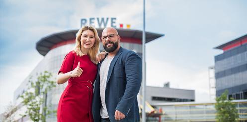 Foto von zwei Mitarbeitern mit REWE Zentrale im Hintergrund